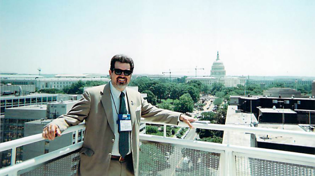 SIg buster standing on a balcony with the capital of DC in the background.