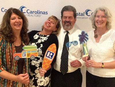 Sig with a group at the Coastal Carolina's realtors event in an informal setting with beach oriented props